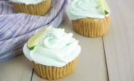 three margarita flavored cupcakes sitting on a grey wood table with a striped linen