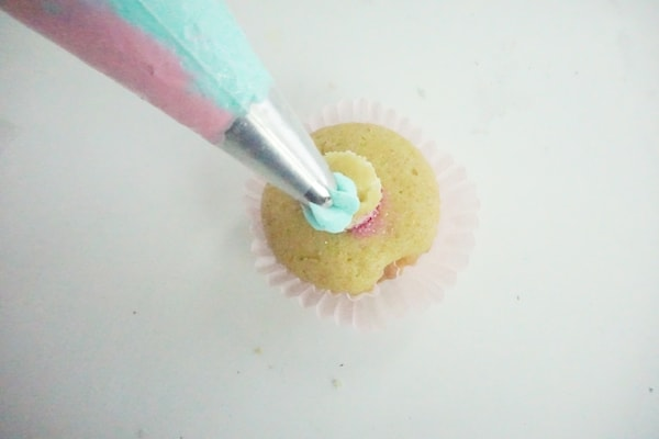 pink and blue icing being piped onto a cupcake
