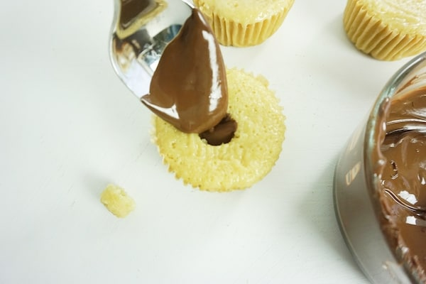 spoon drizzling chocolate into a well inside a cupcake with more cupcakes and a bowl of melted chocolate in the background on a white table