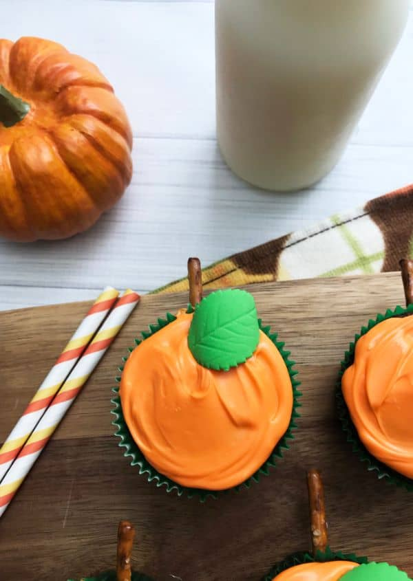 cupcakes decorated with orange frosting, green candy leaf, and pretzel stem to look like pumpkins on a wood slat next to two straws with a pumpkin and  a glass in the background