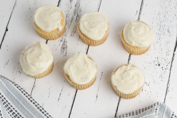 white cupcakes topped with vanilla frosting on a white wood table with a gray linen next to them