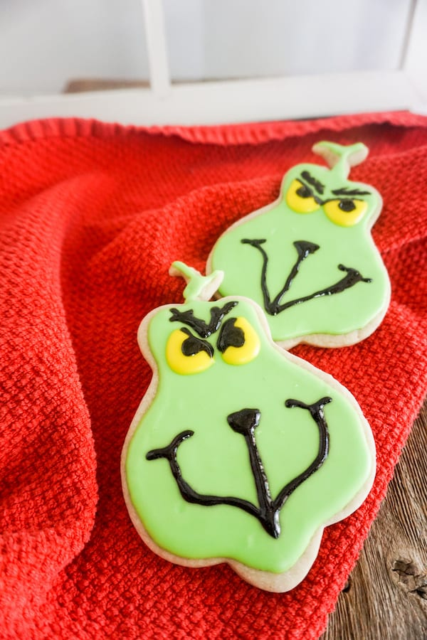 Two cookies made in the shape of the grinch with green, yellow, and black frosting piped on to look like the grinch's face, all on a red blanket.
