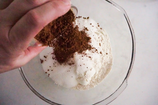 a hand pouring baking cocoa into a glass bowl of flour and sugar