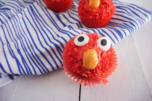 a closeup of a cupcake made to look like Elmo with red frosting, candy eyes and an orange starburst as a nose, on a wood table and a white and blue striped linen with two more cupcakes in the background