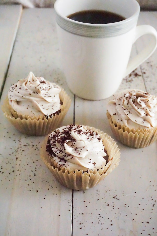 coffee cupcakes topped with frosting and sprinkled with coffee grounds on a table with a cup of coffee in the background
