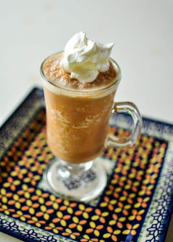 Caramel Pumpkin Spice Frappuccino in a glass mug topped with whipped cream on top of a tray decorated with flowers