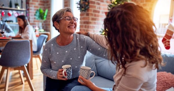 Two women sitting on couch facing each other and holding one another with one arm and a coffee cup in the other hand, holiday decorations in the background