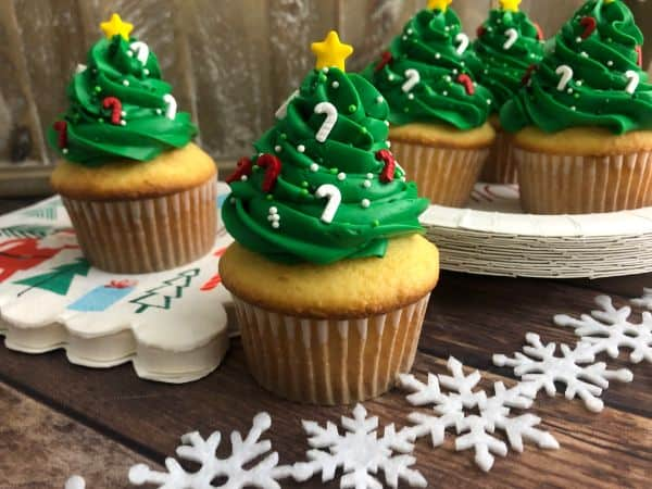 Several cupcakes with green frosting on top in the shape of a Christmas tree, with candy cane sprinkles and a star on top. Snowflakes are in the background.