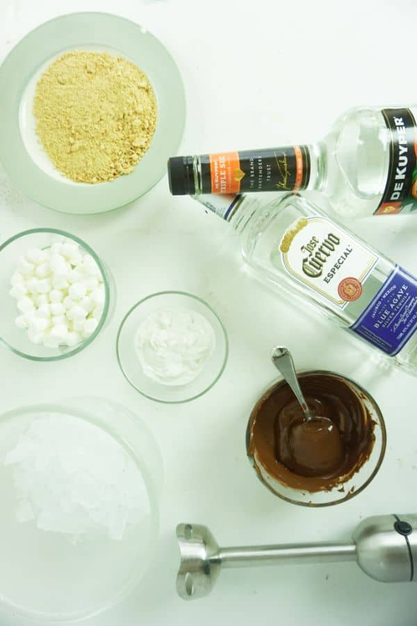 bottles of tequila and triple sec, bowls of coconut cream, melted chocolate chips, ice, crushed graham crackers, marshmallows, immersion blender all on a white table