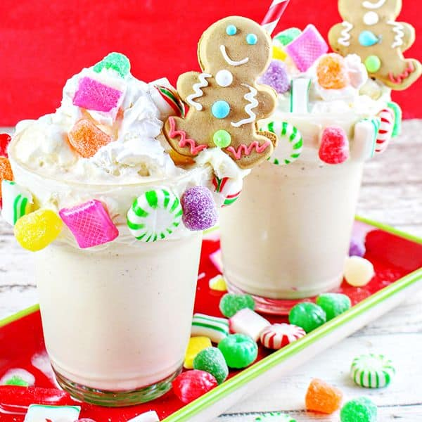 gingerbread house milkshake in two glasses topped with a gingerbread man and colorful hard candies on a red tray with more candies on the tray