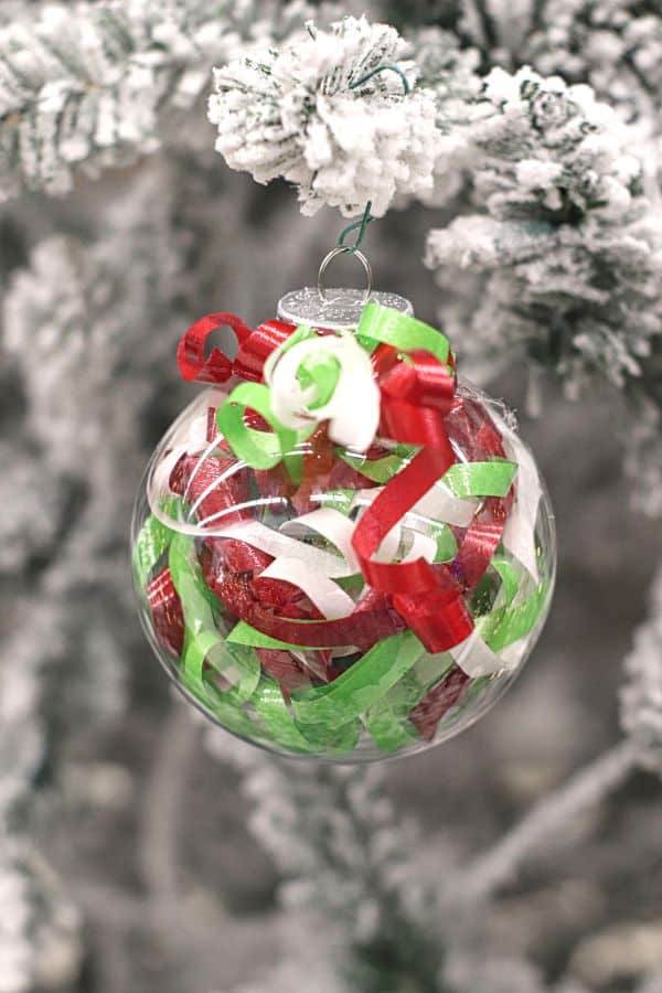 a clear ornament filled with curled ribbon hanging from a flocked Christmas tree
