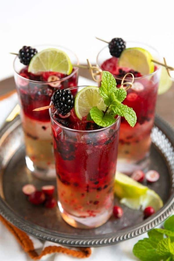 three glasses of Blackberry Cranberry Moscow Mule topped with skewer of blackberries and lime slice on a silver tray