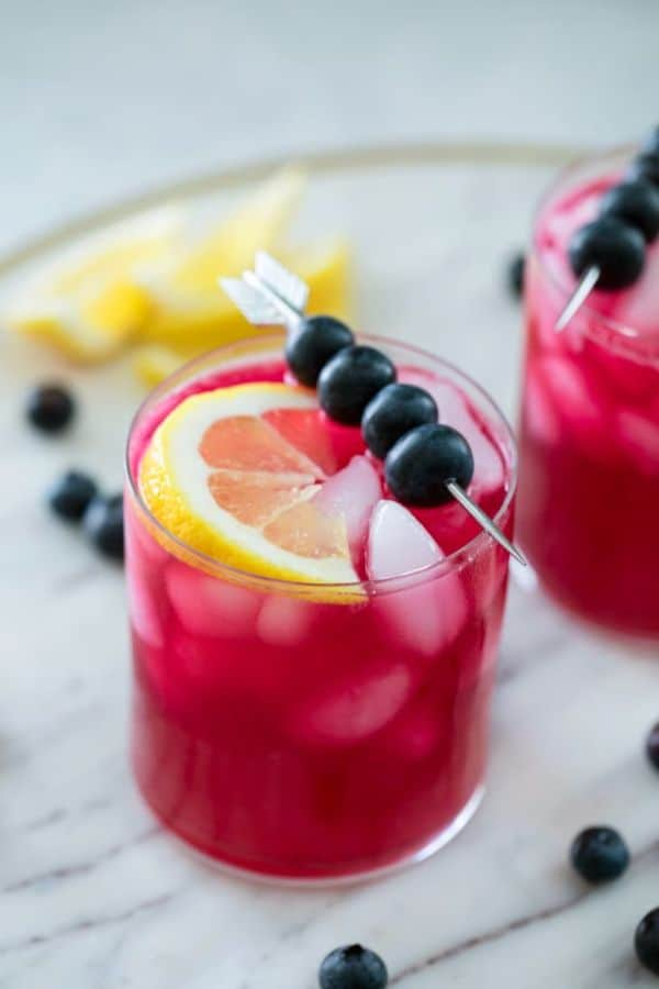 blueberry vodka lemonade in glasses topped with a lemon slice and skewer of blueberries with more blueberries and lemon slices on the counter