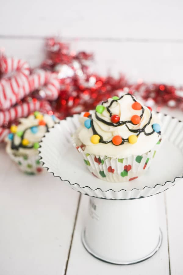 cupcake topped with white frosting, multi-colored candy balls with black frosting in between to look like Christmas lights on a cake plate with another cupcake and candy canes in the background