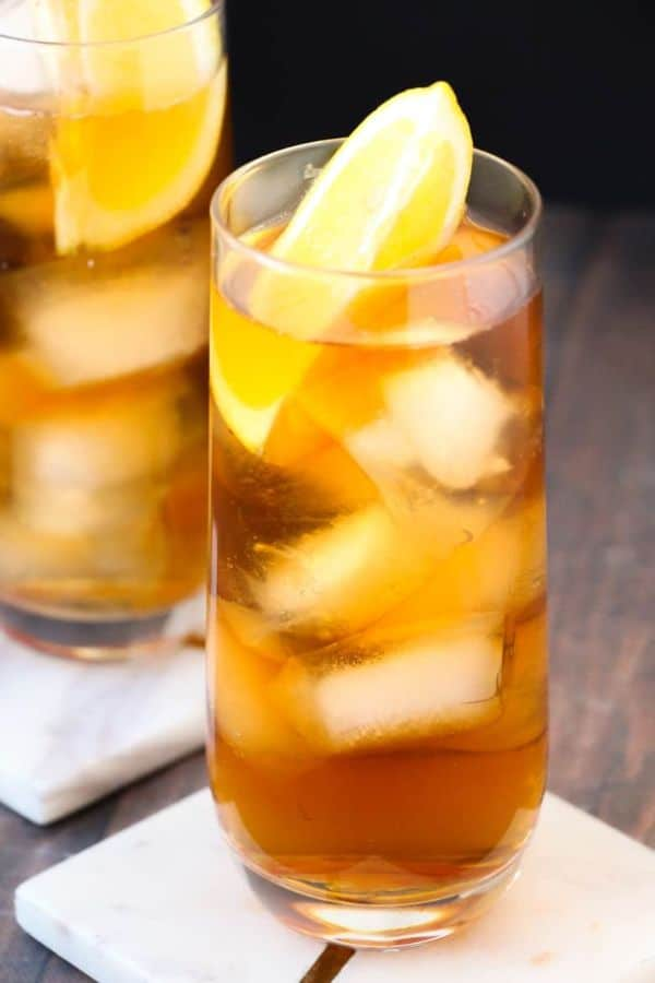two glasses of long island iced tea topped with lemon slices on white coasters on a brown table