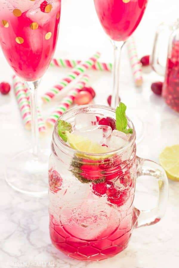 Cranberry Pomegranate Mojito in a glass mason jar with other glasses in the background with decorative paper on a counter
