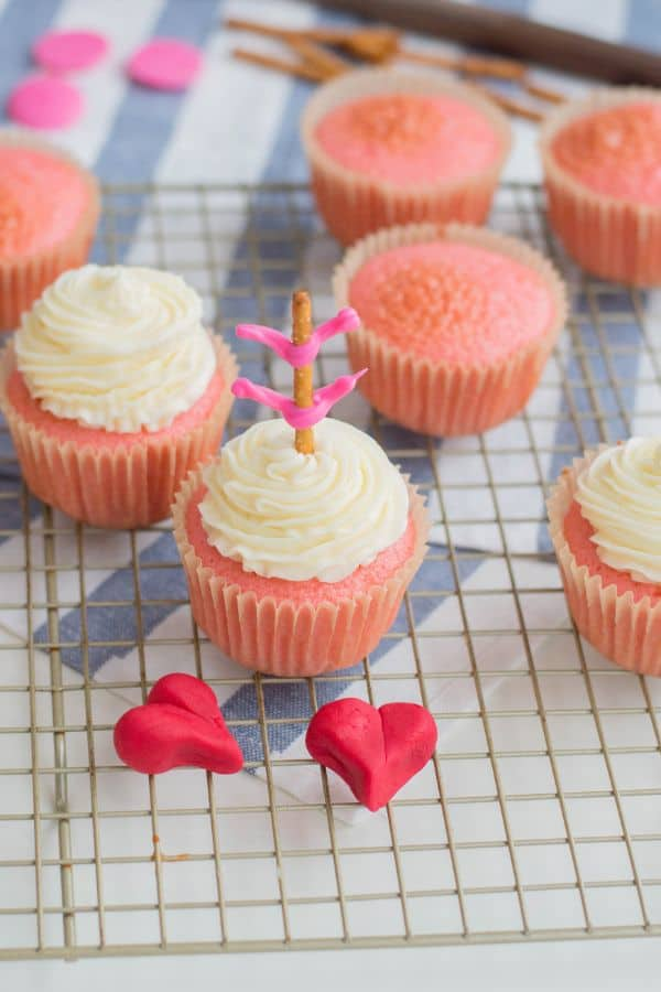 pink cupcakes, 3 topped with white frosting, and one topped with a pretzel stick with pink frosting on it to look like an arrow, next to two red fondant hearts on a wire rack on a blue and white striped cloth on a white table