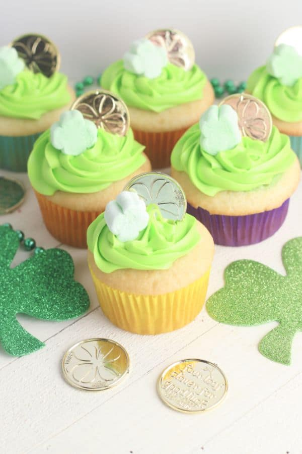 white cupcakes decorated with green frosting, a shamrock marshmallow and gold coin, on a wood table with more shamrocks, gold coins, and green beads on it