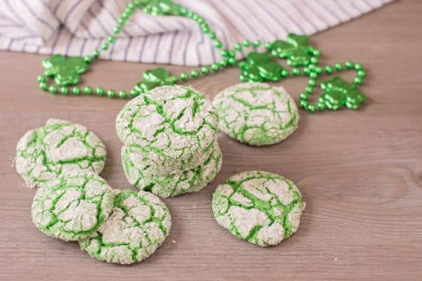 green cookies on a brown table with green beads with clovers on them and a cloth in the background