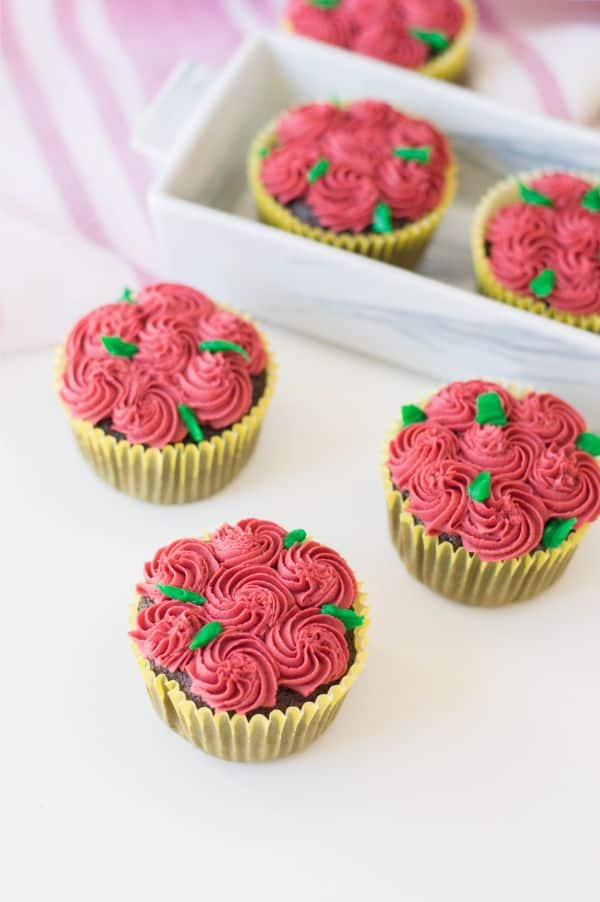chocolate cupcakes decorated with red frosting to look like roses and green frosting for the stems on a white table with more cupcakes and a pink and white cloth in the background