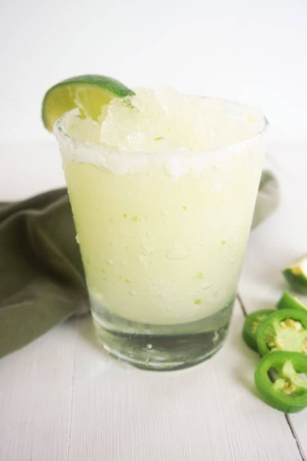 skinny jalapeno margartia in a glass rimmed with salt and topped with a lime slice with slices of jalapeno and a green napkin on the white wood table next to it