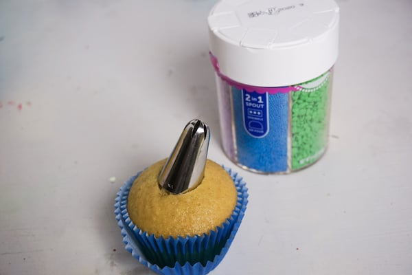 a cupcake with a piping tip in the middle next to a jar of sprinkles