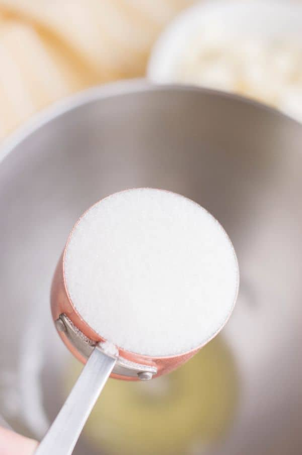 sugar in a measuring cup above a mixing bowl with egg whites and cream of tartar in it