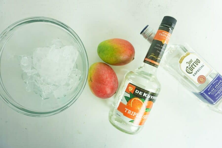 ice in a glass bowl, two mangoes, a bottle of triple sec and a bottle of tequila all on a white background