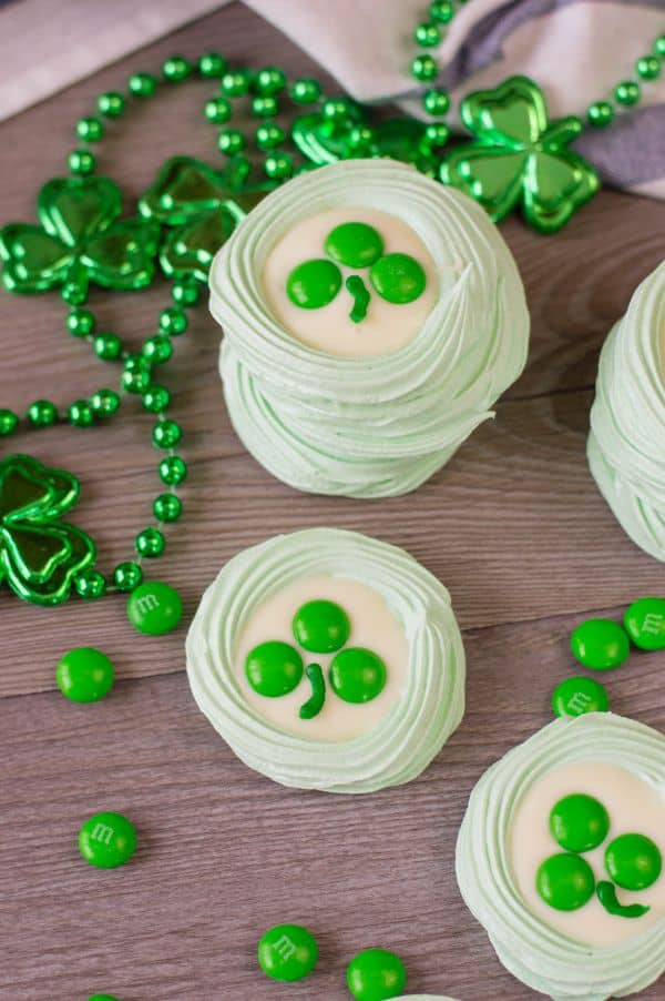 green meringue cookies topped with melted white candy melts, three green m&ms, and a stripe of green frosting to look like a clover, all on a brown table next to green beads with shamrocks on them