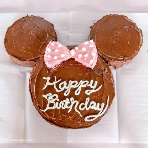 three cakes in the shape of minnie mouse with the words Happy Birthday in white frosting on the center cake