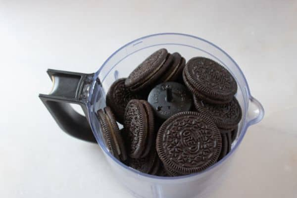 oreo cookies in a food processor on a white counter