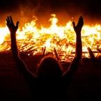 A Burning Man participant pays homage to the Temple of Whollyness as it burns at the conclusion of the 2013 Burning Man arts and music festival in the Black Rock desert of Nevada
