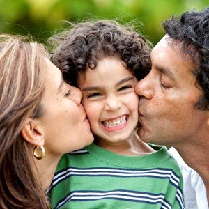 parents kissing a laughing child's cheeks | Life coaching for moms of special needs kids who struggle with behavior problems