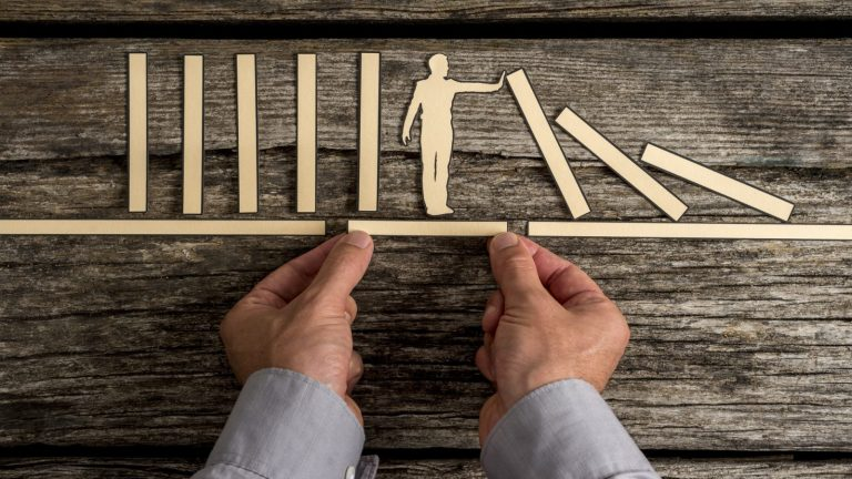 Businessman stopping the domino effect
