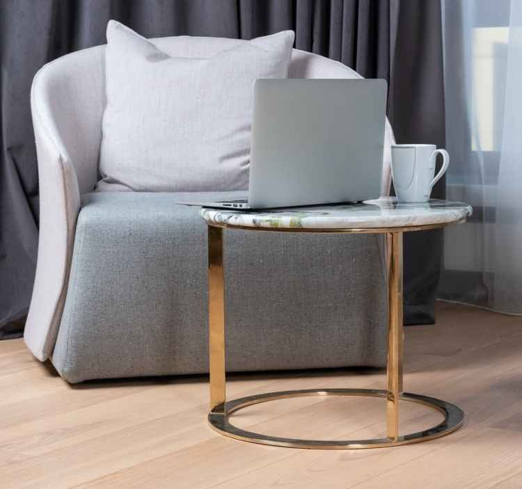 laptop and coffee mug placed on small table near armchair