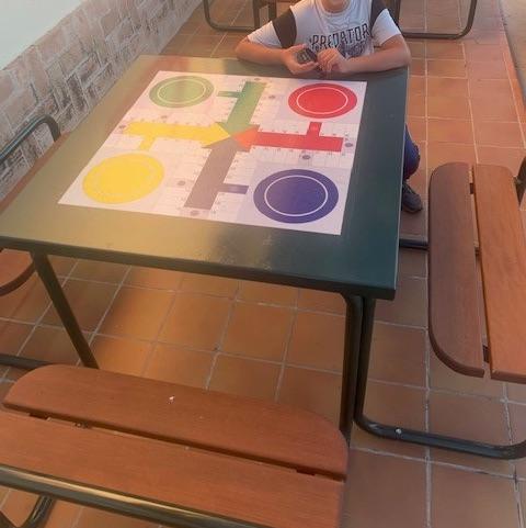 niño jugando en mesa urbana de parchis