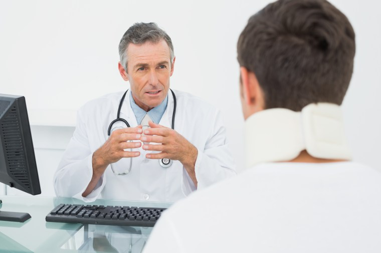 Male doctor in conversation with patient at desk in medical office