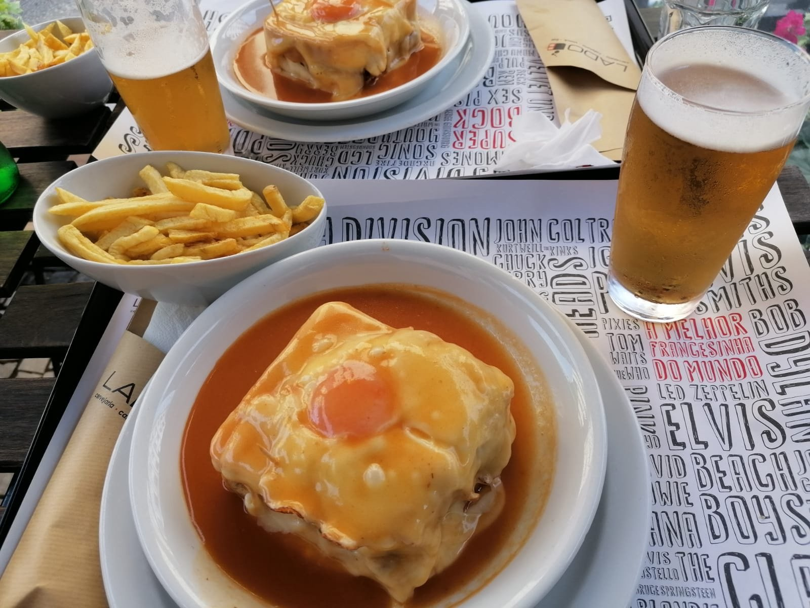 Food in Porto - Francesinha on a plate next to french fries and a glass of beer