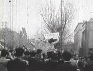 국회의사당 앞의 데모, 한 여대생이 무등을 타고 구호문을 치켜 들었다.1960년 4월 19일