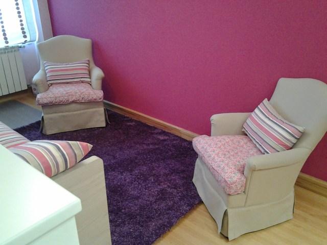 Conjunto butacas tapizadas y alfombra, pared color fresa