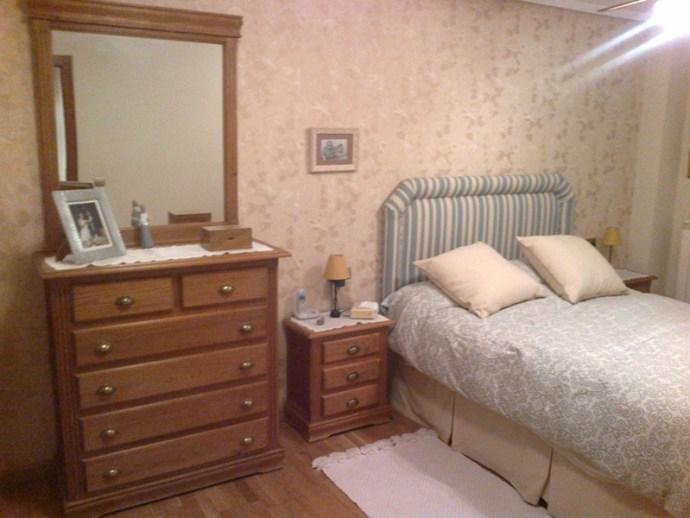 Dormitorio cabecero tapizado de rayas azules y empapelado en beige