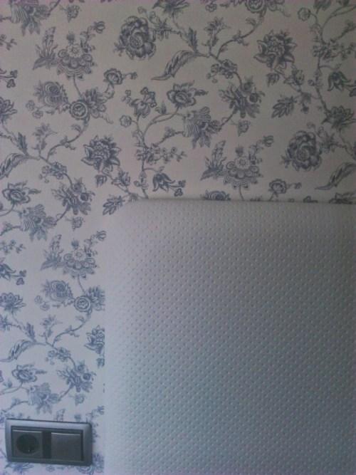 Papel pintado en azules con cabecero de cama tapizado blanco