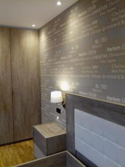 Papel pintado cabecero de cama, muebles color piedra y aplique a pared