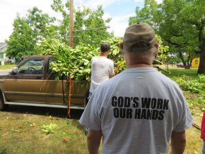 "Transformations | A volunteers t-shirt read, ""God Work, Our Hands."""