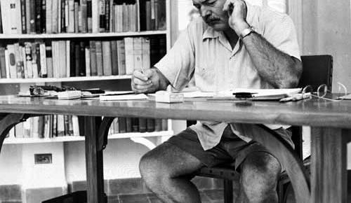 ernest hemingway black and white short pants writing at desk finca background bookshelves