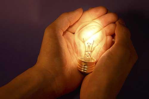Light bulb in cupped hands innovation www.servetolead.org