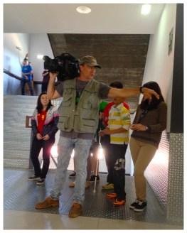 El cámara de televisión prepara al grupo para grabar la entrada en clase.