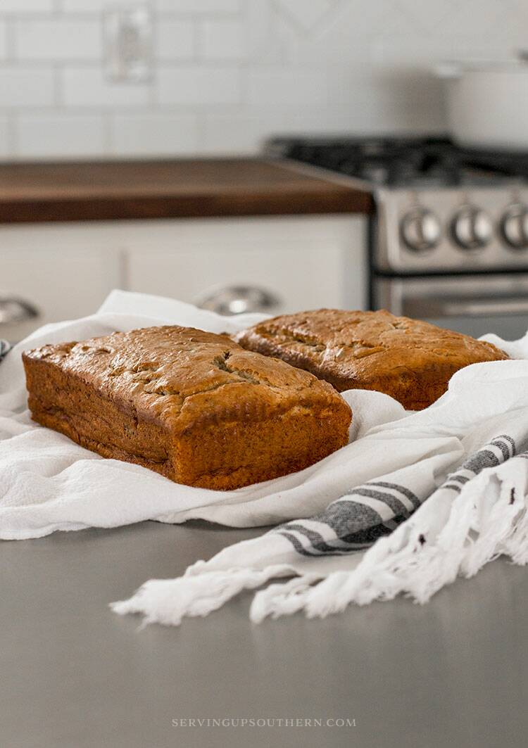 Two loaves of banana nut bread on flour sack towels sitting on a stainless steel island top.