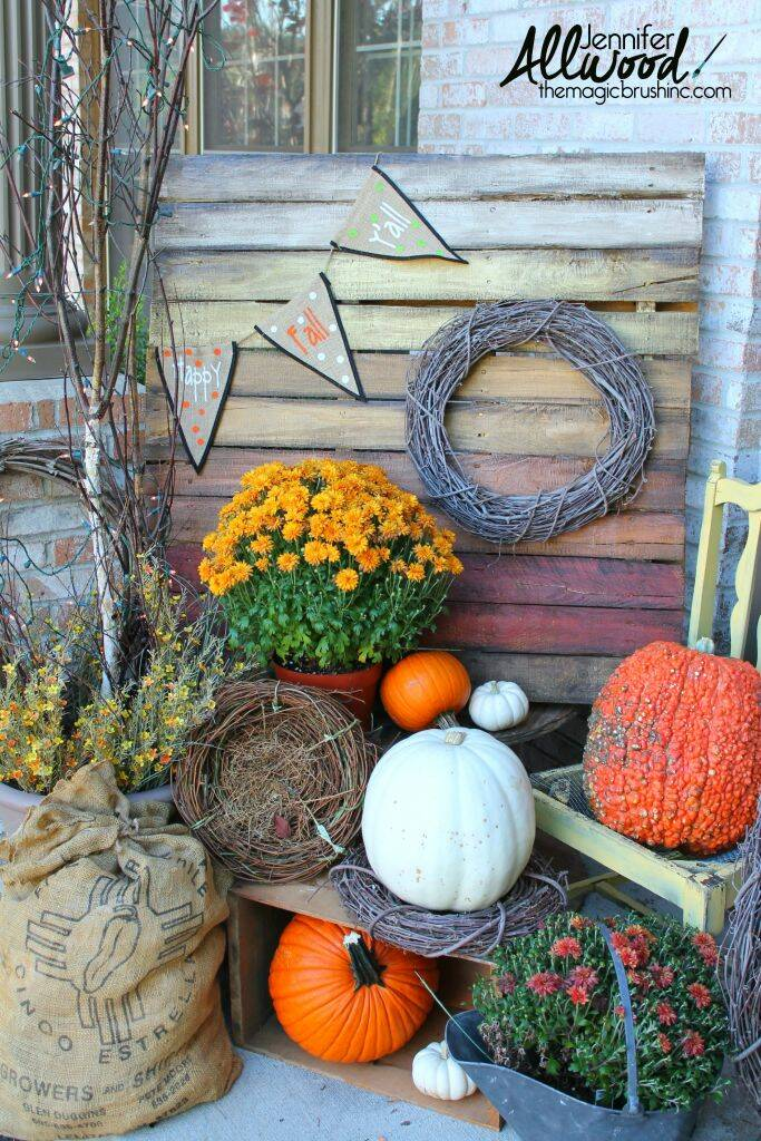 Wooden pallet painted in fall colors propped on porch with pumpkins.