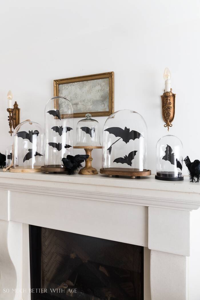 Mantle with bat cutouts displayed in glass cloches.
